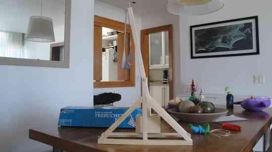 """Foto de um """"Trebuchet"""" em miniatura na sala, onde Eduardo dá suas aulas."""