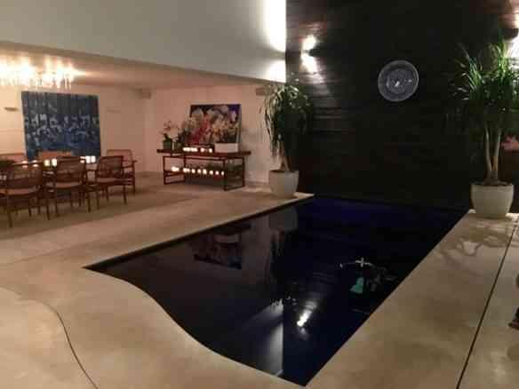 """Primeiro e """"grandioso detalhe: o terraço que dá para os fundos do apartamento virou uma deliciosa sala de jantar junto da piscina coberta, onde o dona da casa se exercita... Reparem na bicicleta submersa!"""
