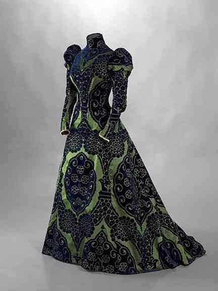 """Este exótico vestido, também de Worth, era um """"tea gown"""", como explica o letreiro da mostra, ou um """"vestido de chá""""... Verde esmeralda, cor preferida de Élizabeth, e azul pavão, ele é de seda, veludo e """"renda valenciana"""" é outra atração de seu guarda-roupa!"""